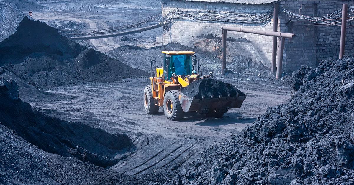 Колесный погрузчик загружает уголь - shutterstock