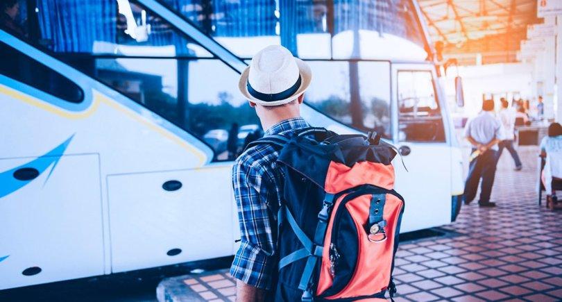 молодой человек путешественник ждёт на автобусной станции - shutterstock.com