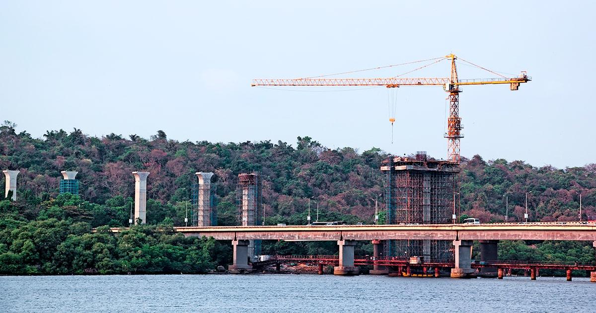 Строительство высоких бетонных опор с использованием башенного крана для нового моста через реку Мандови в Гоа, Индия. shutterstock