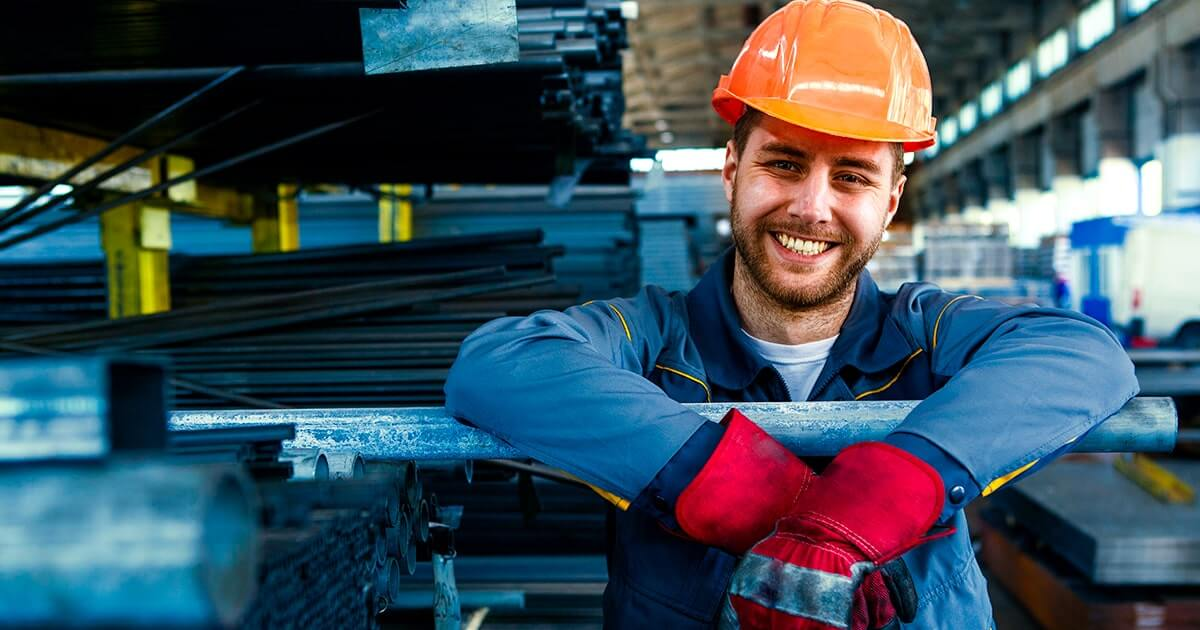 Жизнерадостный молодой работник на фабрике металлообработки.  shutterstock