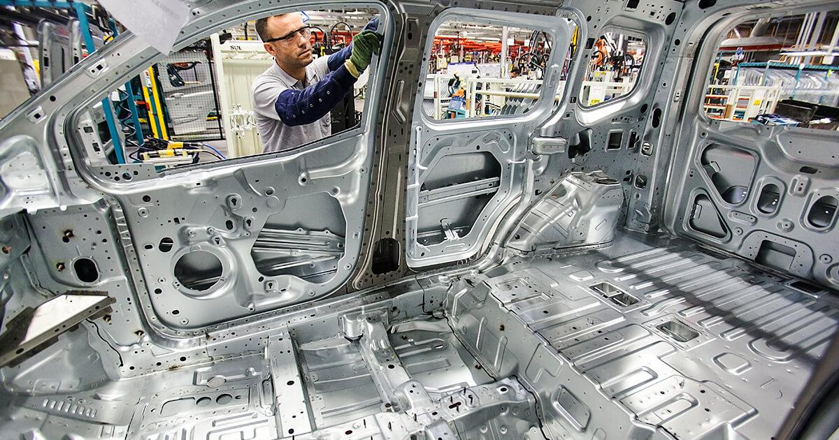 Рабочий проверяет собранный автомобиль на фабрике. Shutterstock.com