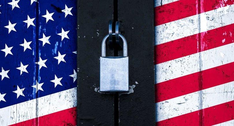 Флаг Соединенных Штатов Америки нарисован на деревянной двери и заблокирован замком. shutterstock
