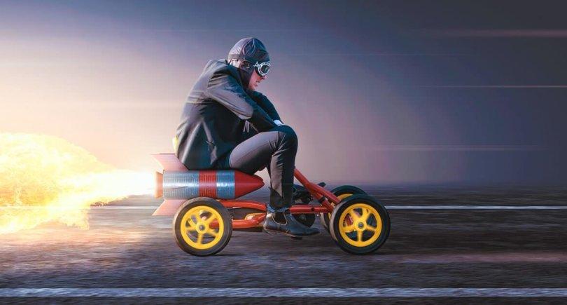 Мужчина в костюме на педальной машине с ракетным двигателем. Shutterstock.com